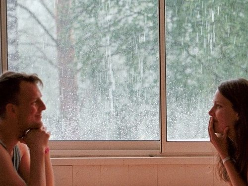 couple looking at each other near window pane