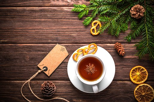 cup of tea on a table near pine cones and fruit