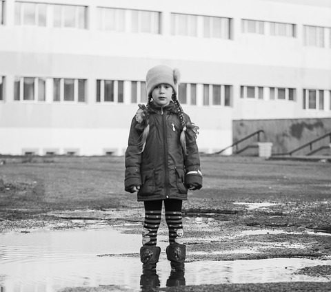 small girl standing in a puddle in black and white
