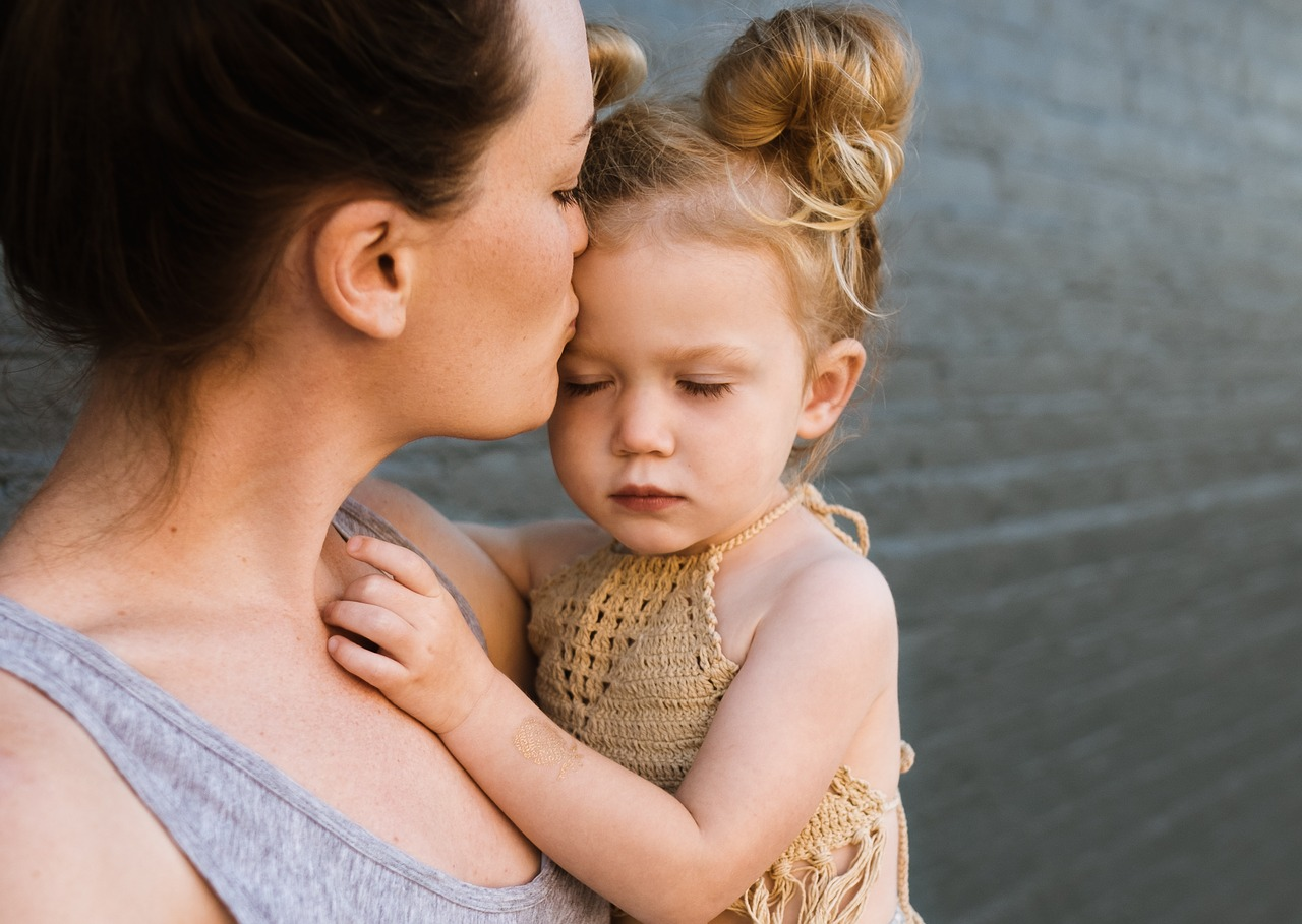 woman kissing a small girl's forehead