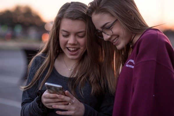 two teenage girls looking at a phone